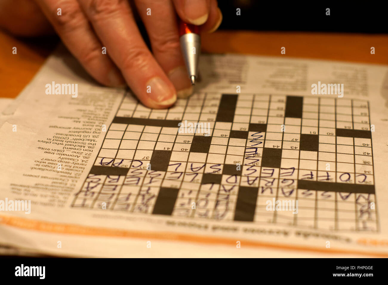 Closeup of a woman's hand, pen, and newspaper crossword puzzle - Stock Image