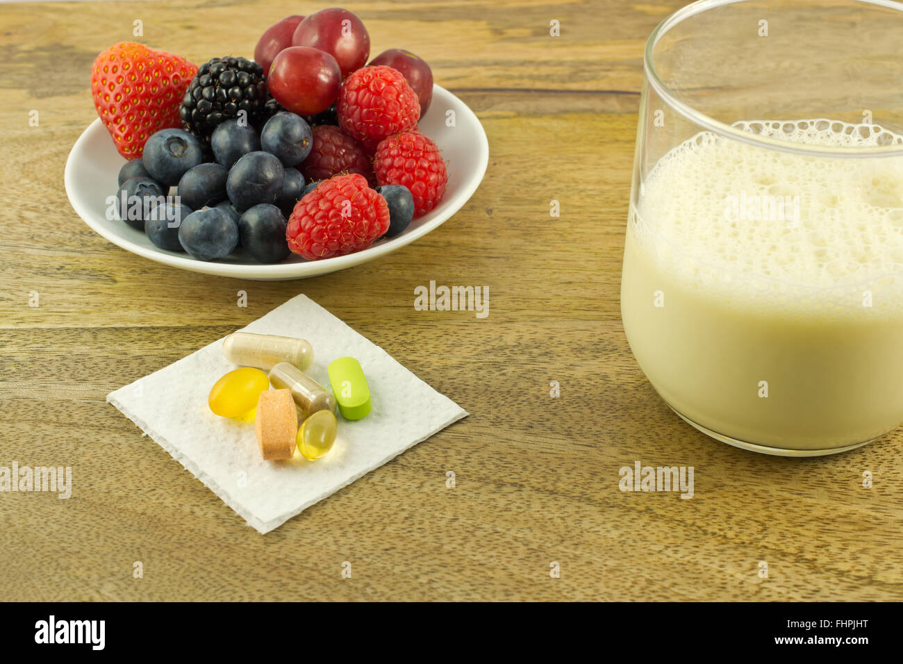 Berries, anti-oxidant supplements and a cup of soy milk on wooden table Stock Photo