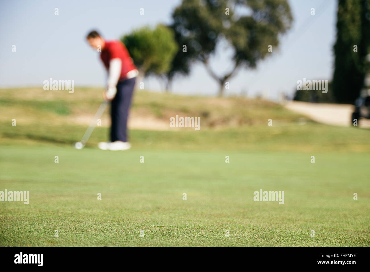 Unfocused golfer playing golf on the green of a golf course - Stock Image