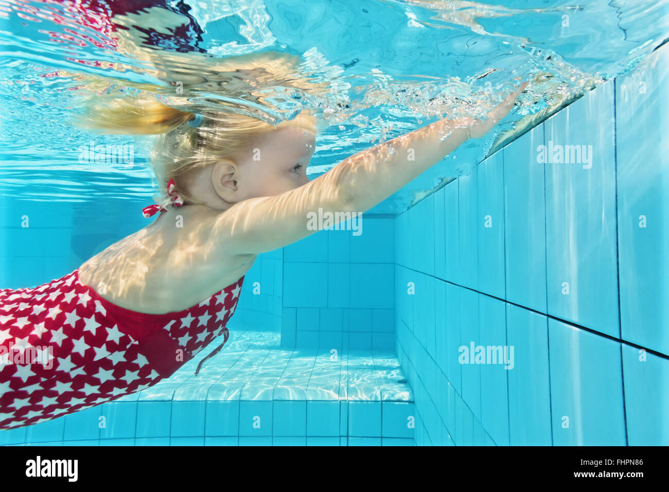 Child swimming lesson - girl learning to dive underwater in pool. - Stock Image