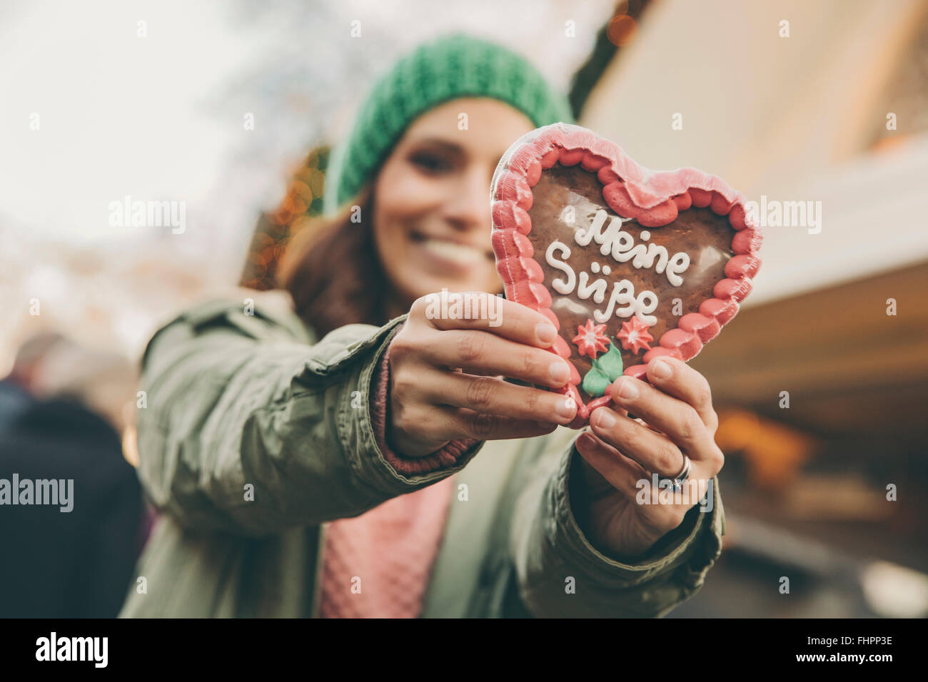 Woman holding up a gingerbread heart on the Christmas Market - Stock Image