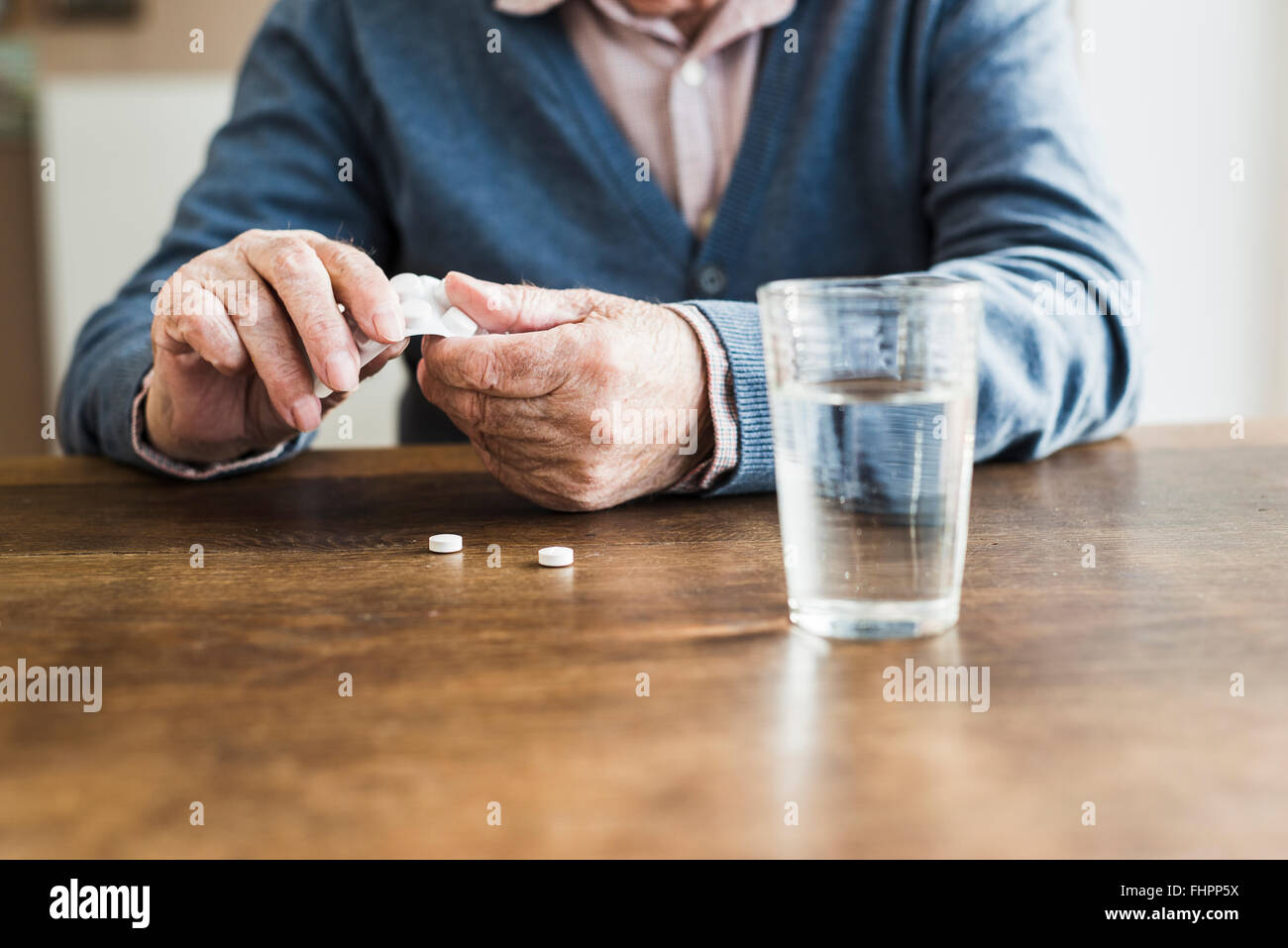 Hands of senior man taking tablets out of blister pack, close-up - Stock Image