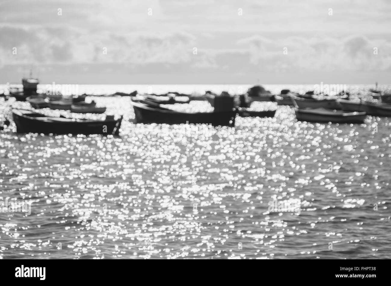 Blurred background of boats against sunlight and sparkles on water surface, black and white image - Stock Image