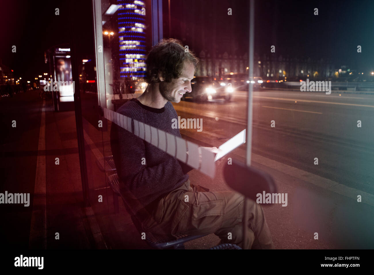 Germany, Munich, man with headphones sitting at bus stop using digital tablet at night - Stock Image