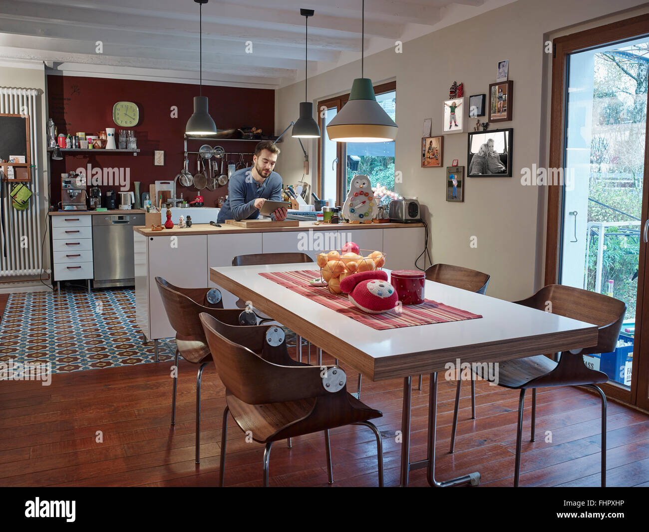 Young man using digital tablet in open plan kitchen - Stock Image