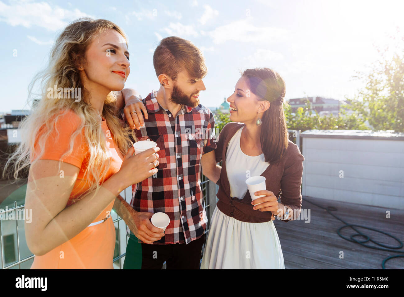 Austria, Vienna, Young people having a party on rooftop terrace - Stock Image