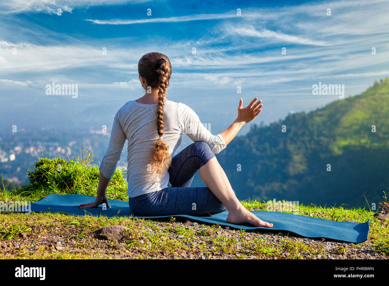 Woman practices yoga asana Marichyasana - Stock Image