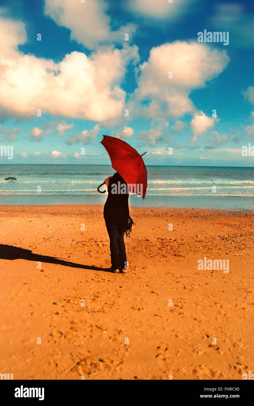 woman with red umbrella standing on sunny beach - Stock Image