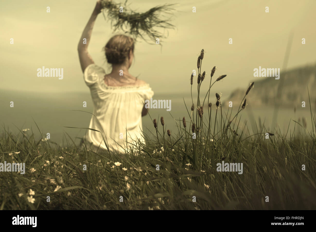 young woman sitting on cliff waving and holding grass awaiting her lover - Stock Image