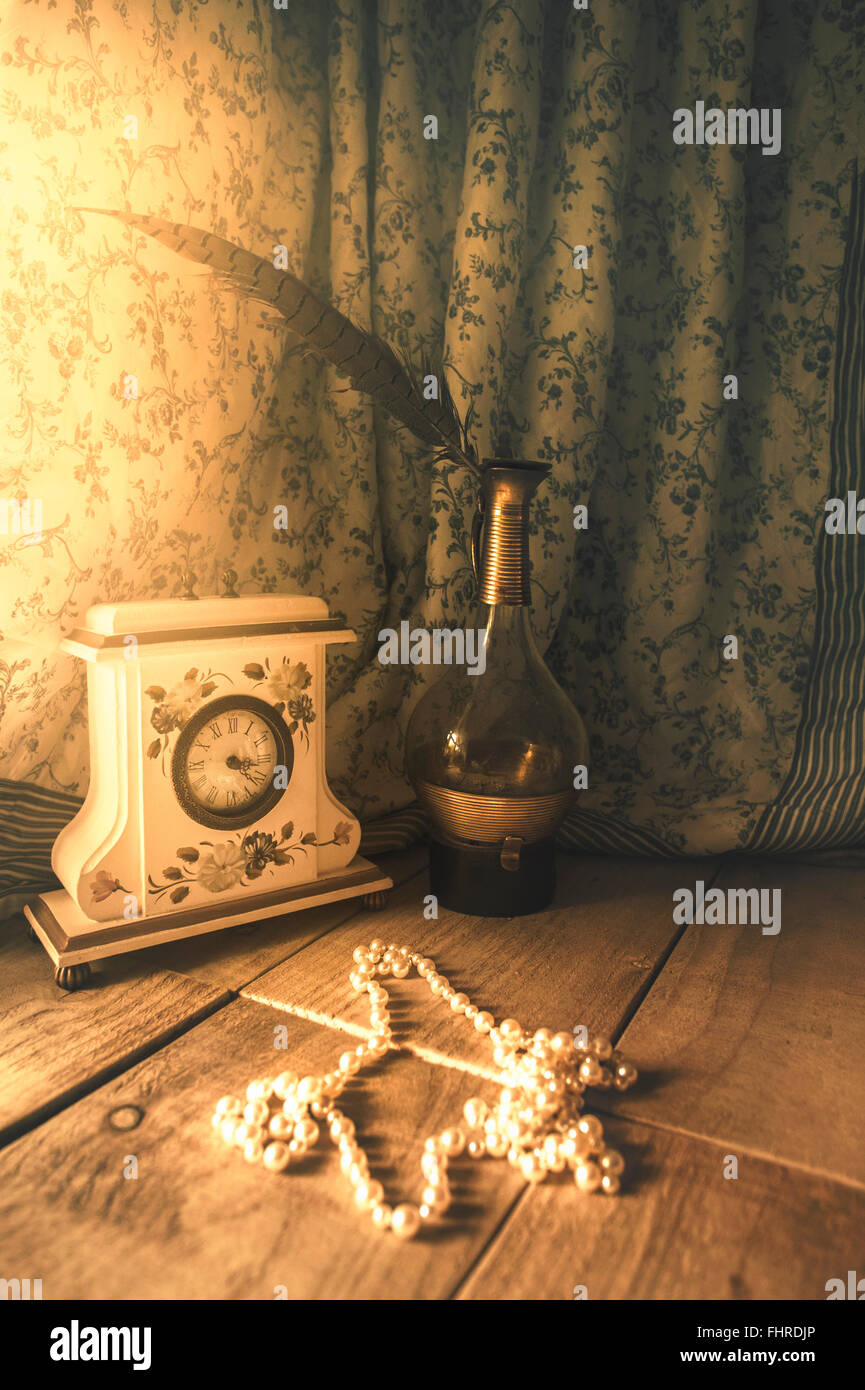 romantic still life with a vintage clock, glass bottle, feather and pearls - Stock Image