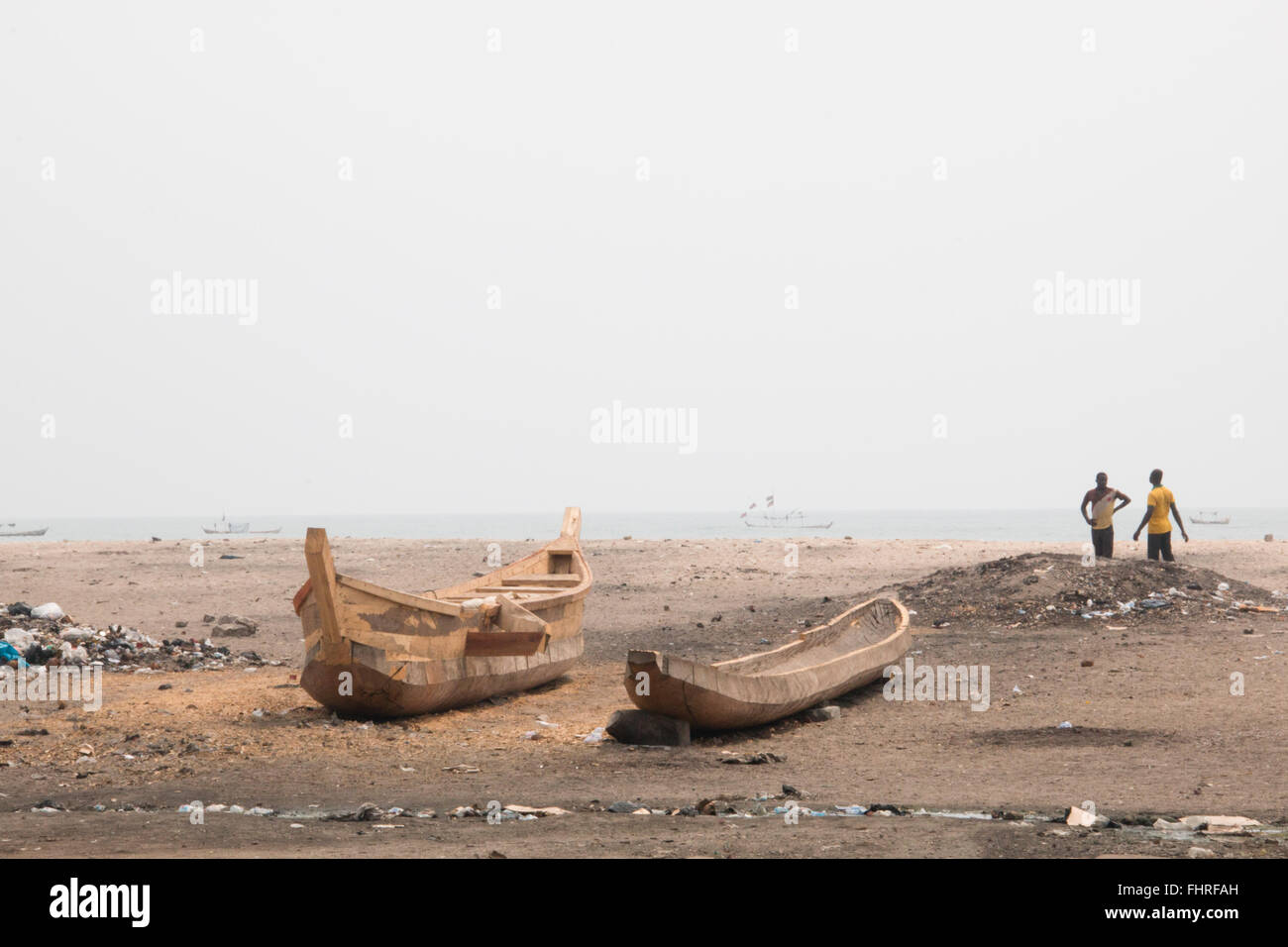 ACCRA, GHANA - JANUARY 2016: People and fishing boats on a beach in Jamestown, Accra, Ghana at the Gulf of Guinea - Stock Image