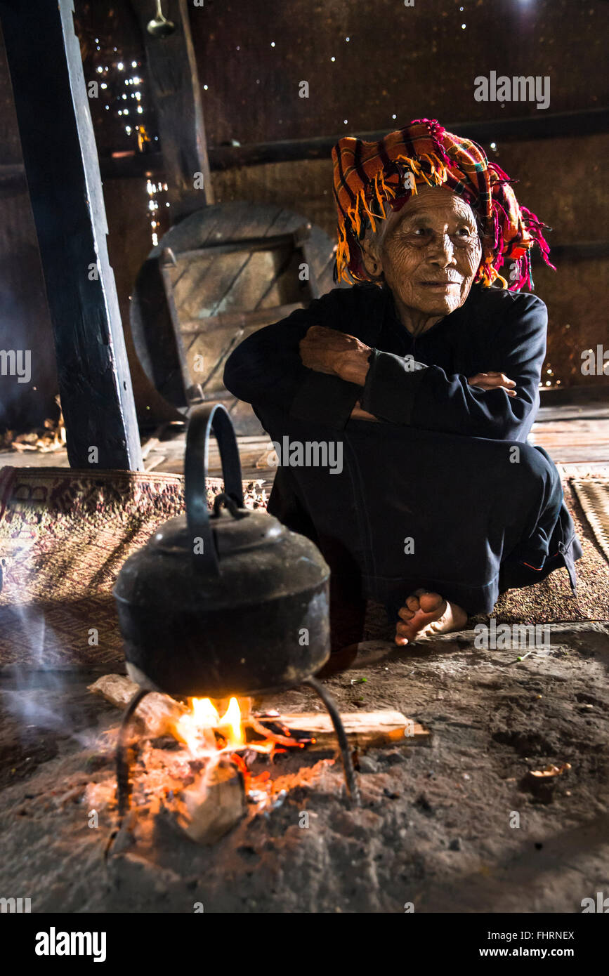 Old woman in the kitchen, kettle on an open fire place in the lodge, mountain tribe or mountain people Pa-O or Pa - Stock Image