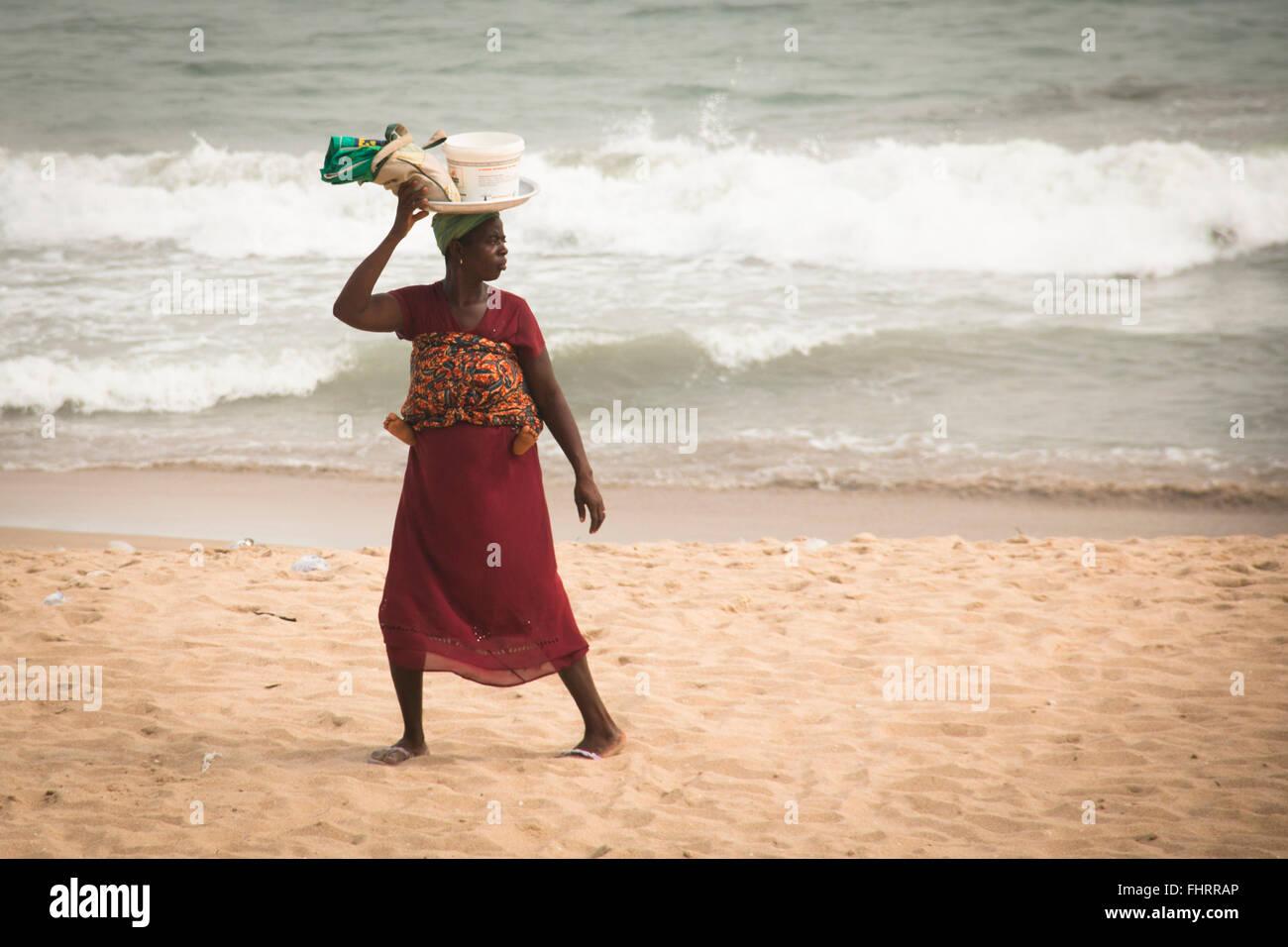 CAPE COAST, GHANA - JANUARY 2016: Woman with a baby on the beach in Cape Coast, Ghana at the Gulf of Guinea - Stock Image