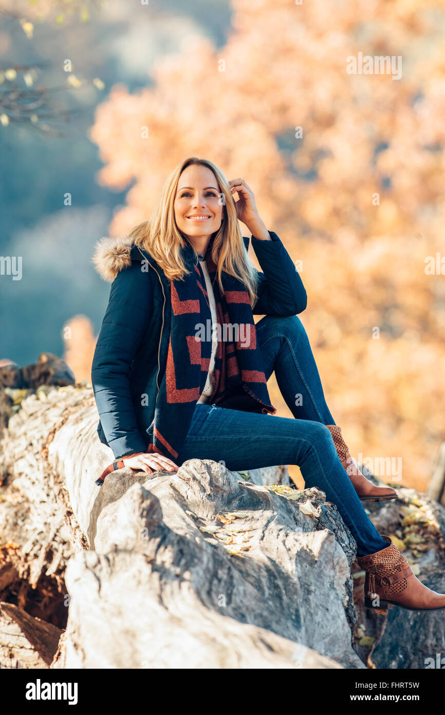 Smiling woman enjoying autumn in a forest sitting on a trunk - Stock Image