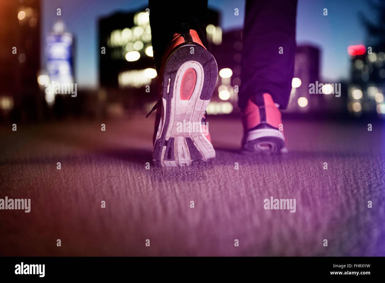 Sneakers of jogging man on tarmac at night - Stock Image