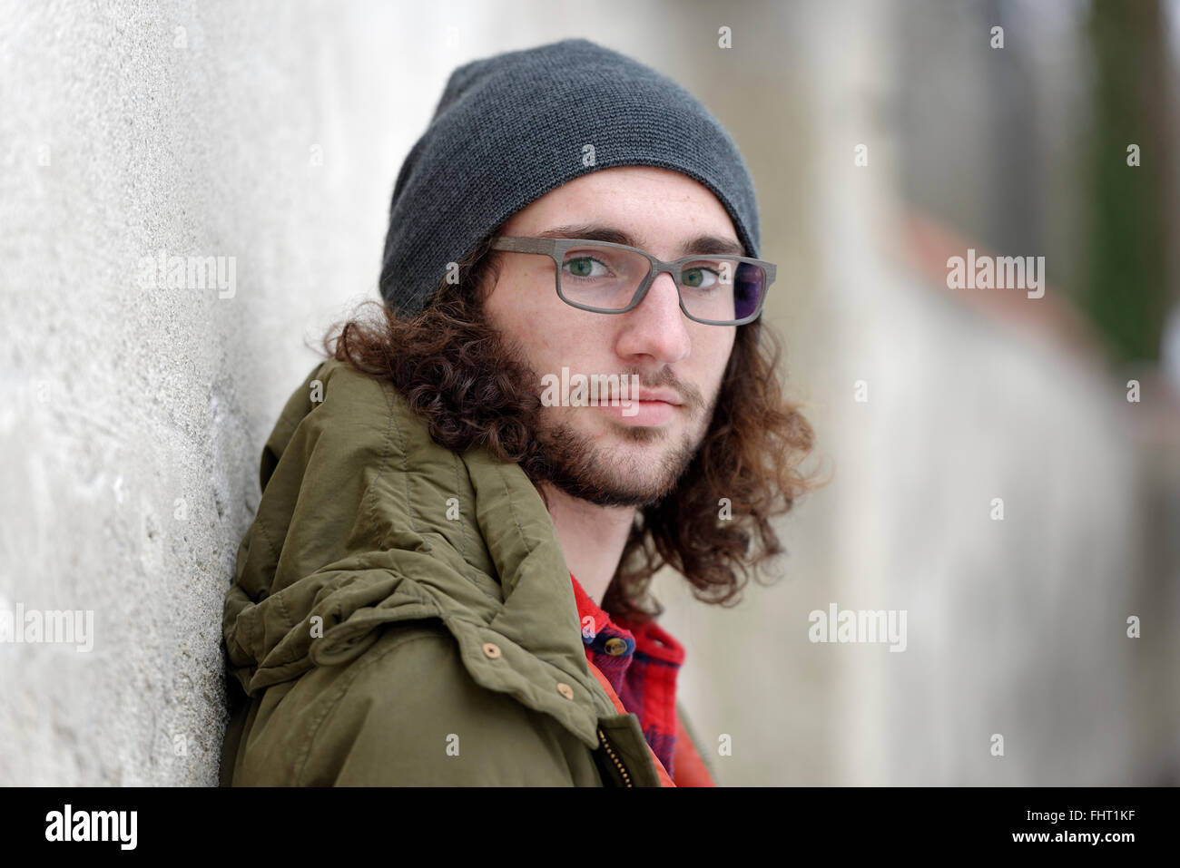 Portrait of relaxed young ma nwith curly brown hair wearing wooly hat - Stock Image