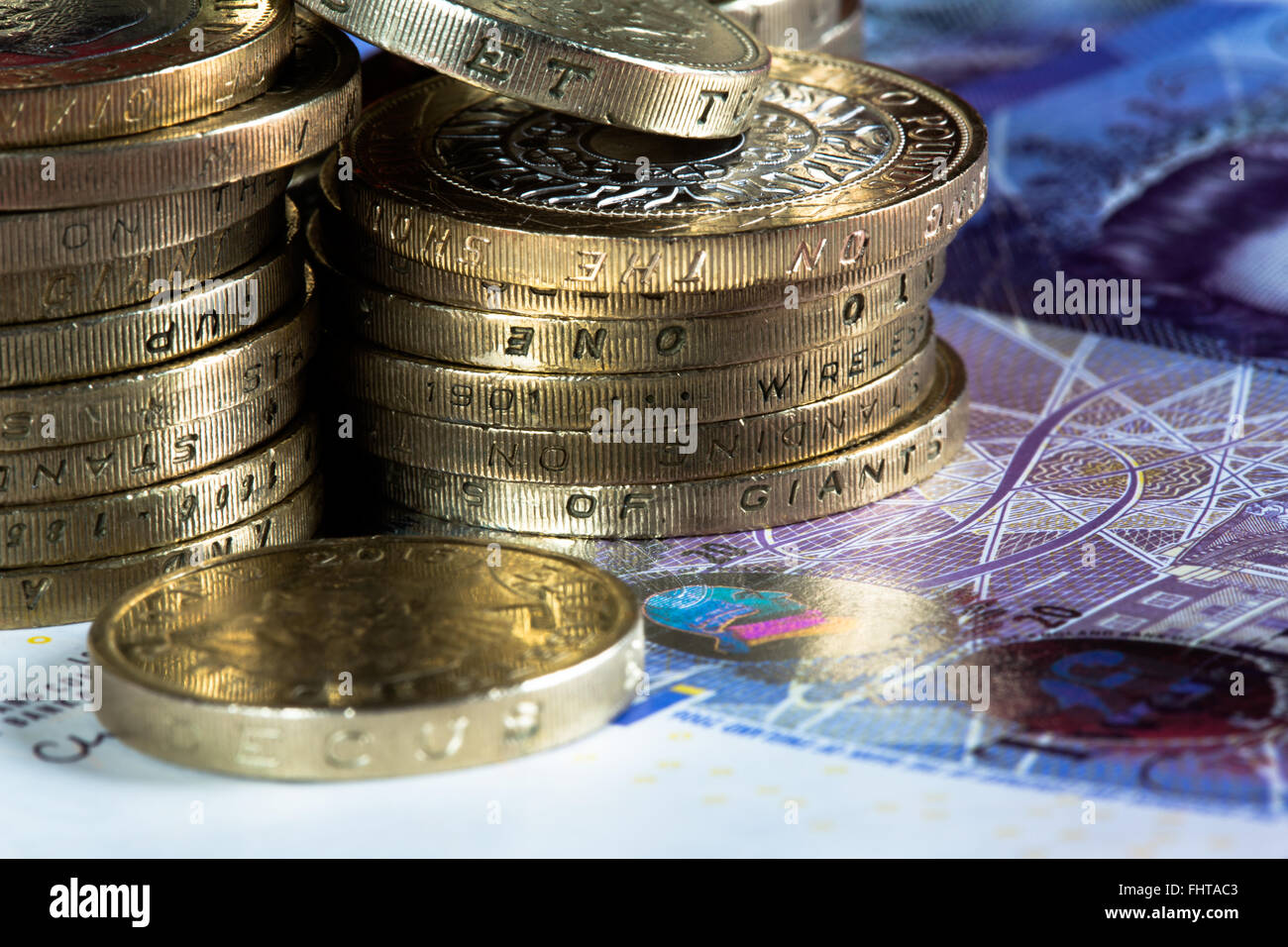 A macro image of coins and notes of the British Realm. Specifically Two Pound coins, One Pound coins and 20 Pound - Stock Image