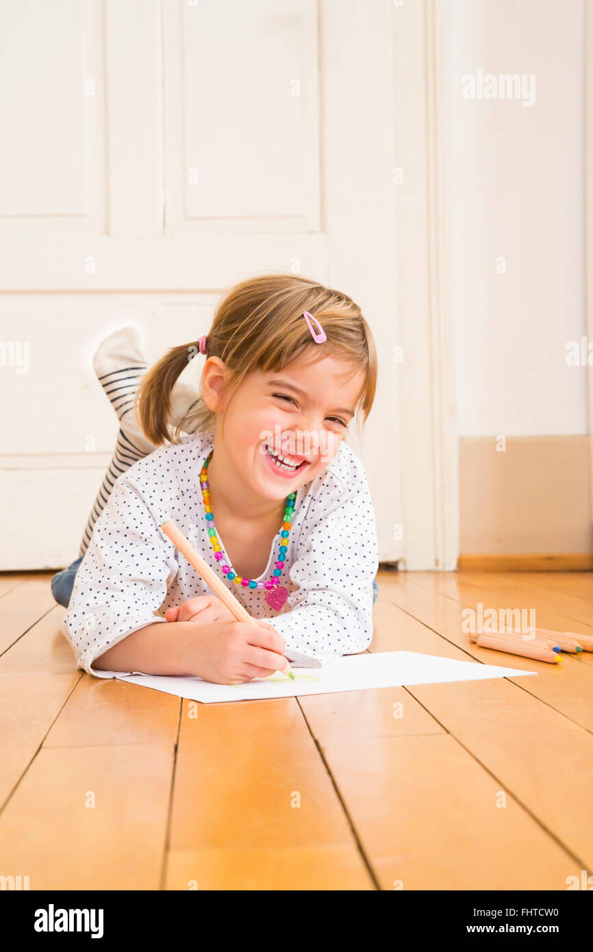 Portrait of laughing little girl lying on wooden floor with crayons and sheet of paper - Stock Image