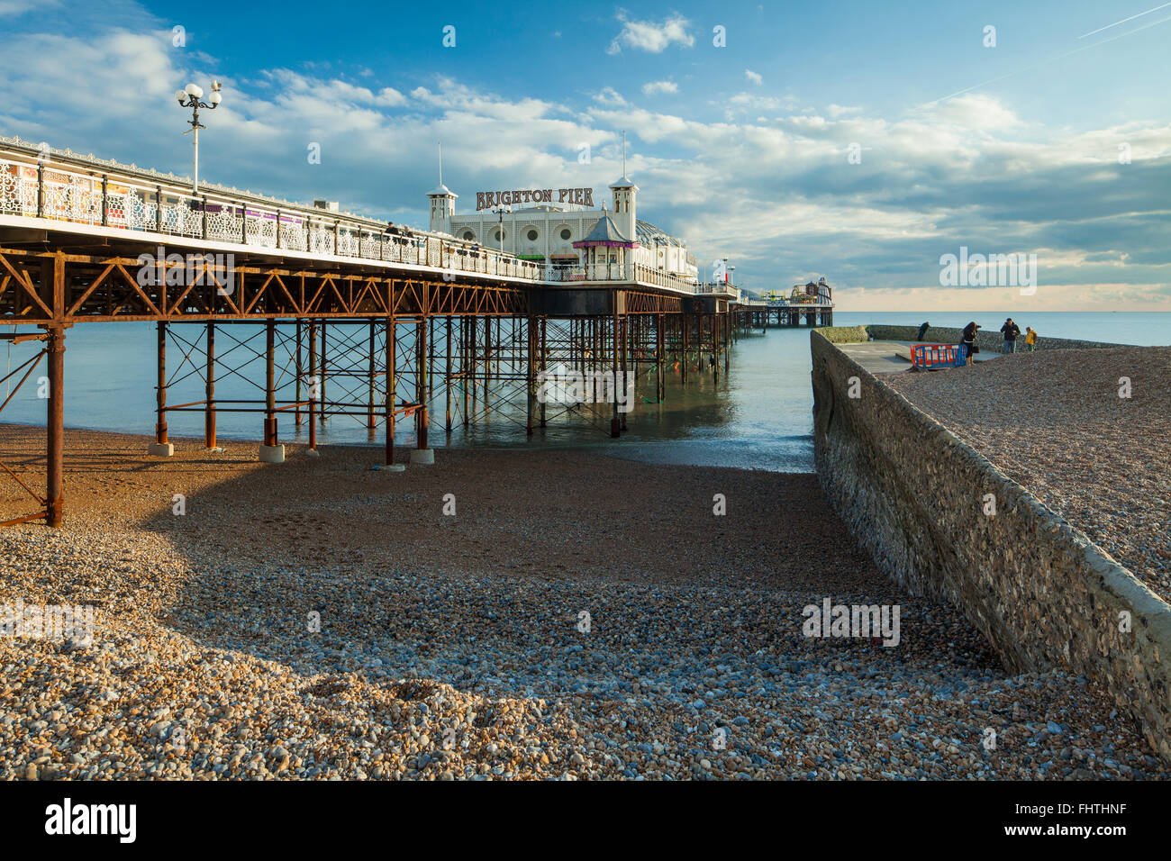 Winter afternoon at Brighton Pier, UK. Pebbles cover groyne after a recent storm. - Stock Image