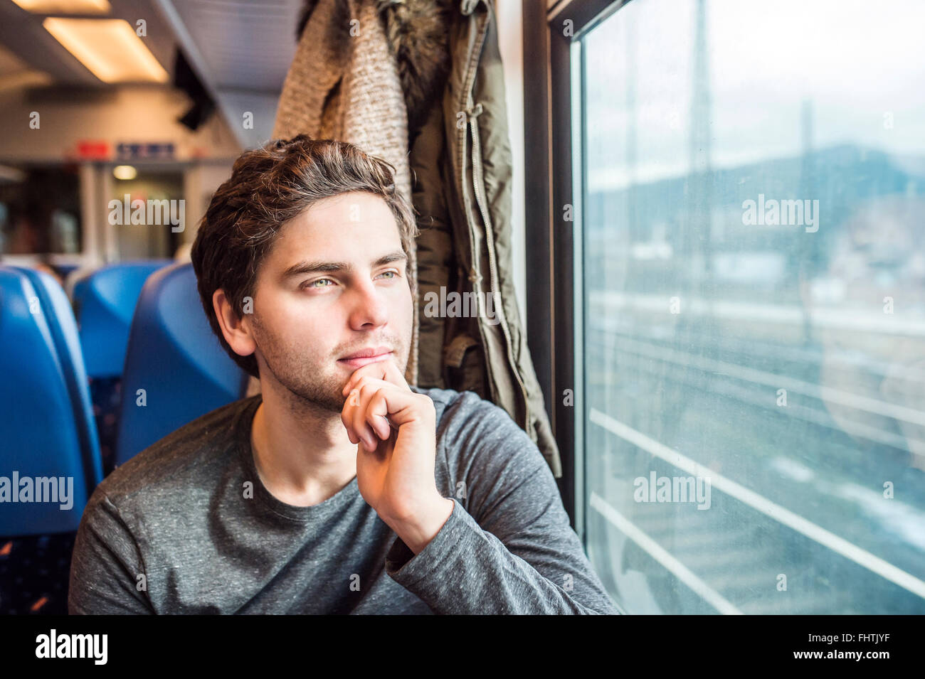 Young man in train car looking out of window - Stock Image