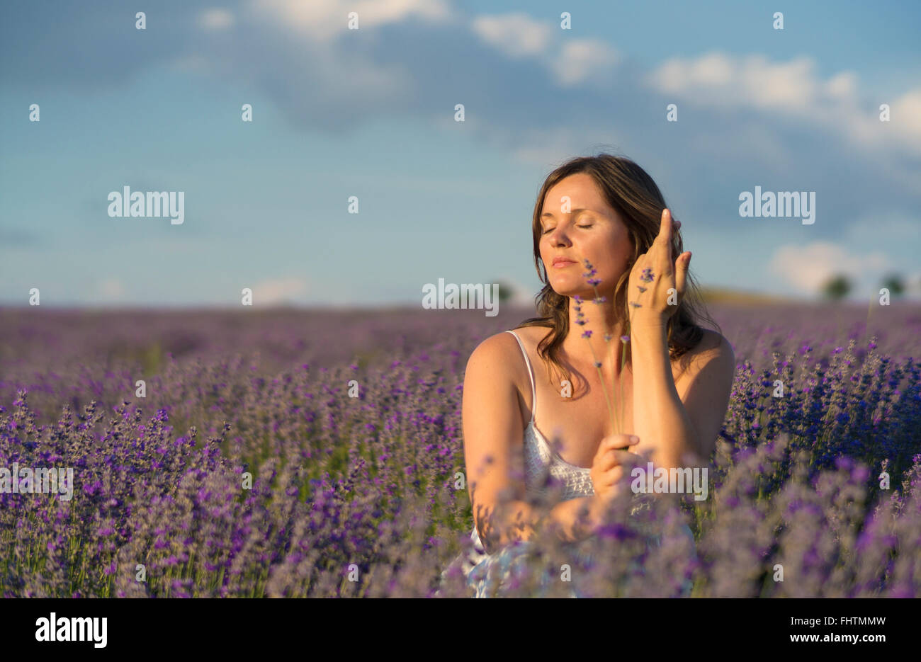 Beautiful young woman holding a bunch of lavender flowers enjoying their fragrance in the middle of a lavender field - Stock Image