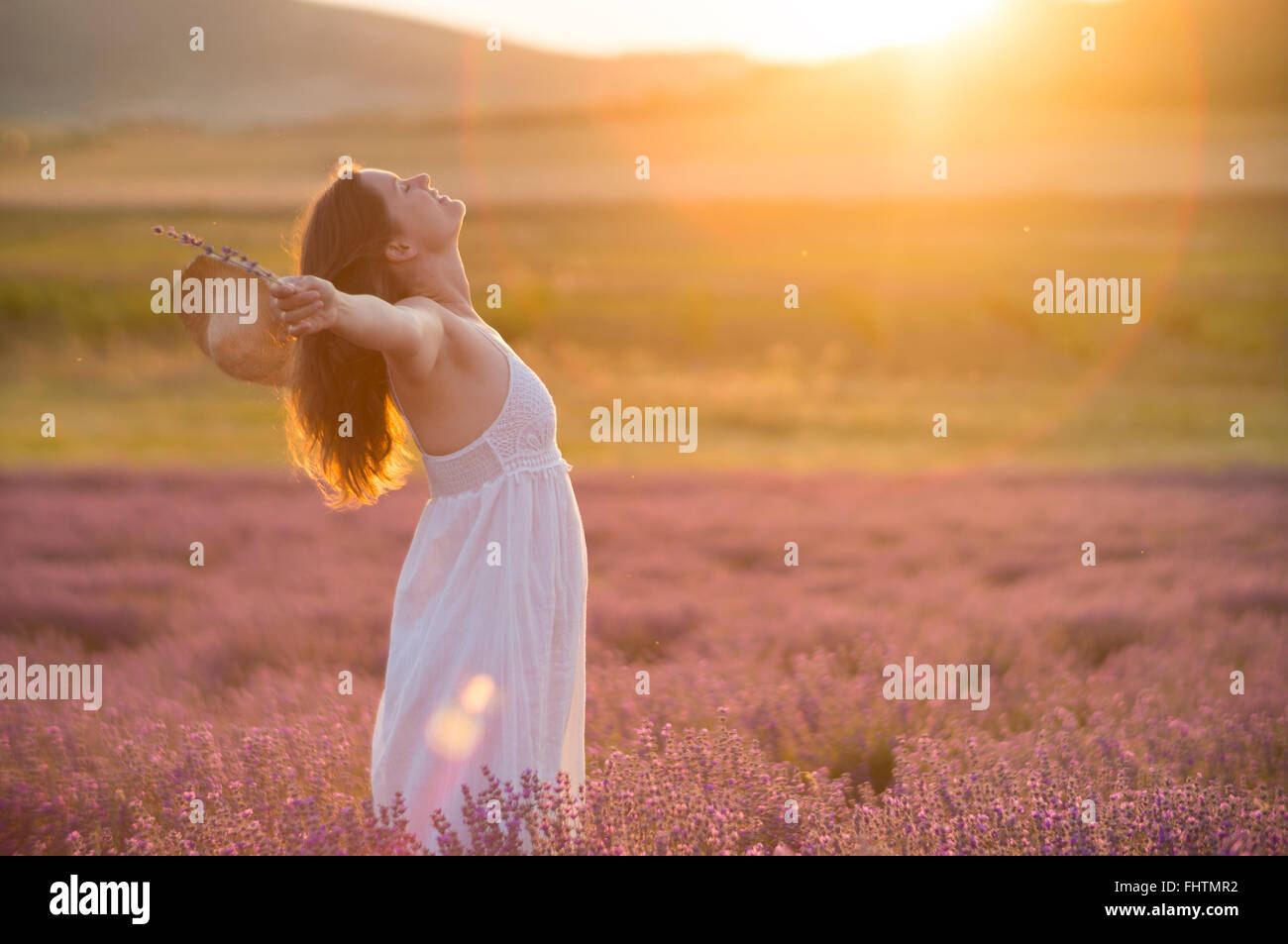 Beautiful young woman with a white dress and a straw hat standing in the middle of a lavender field at in the golden - Stock Image