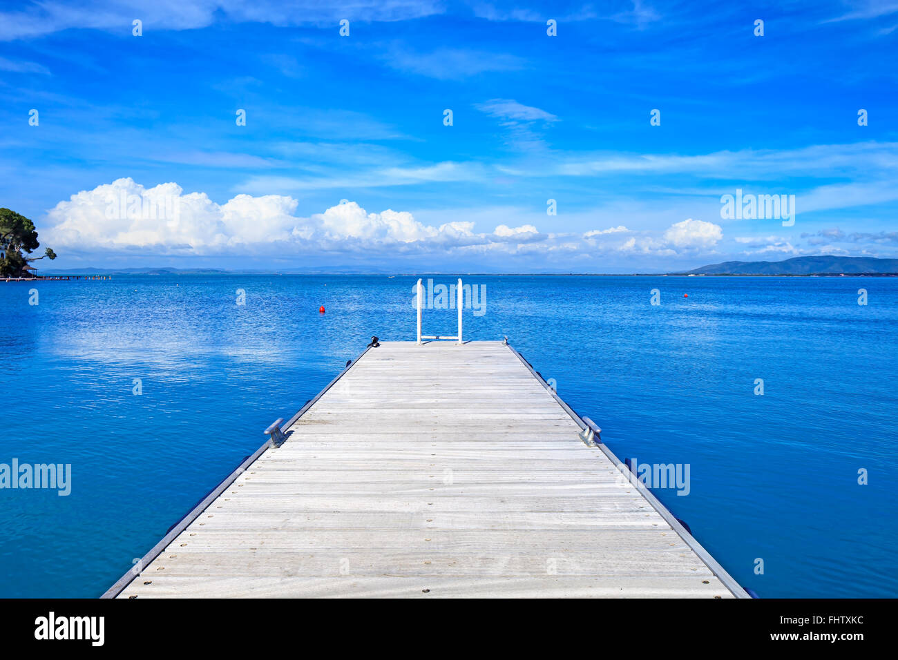 Wooden pier or jetty on a blue ocean and clear sky. Bay beach in Monte Argentario, Porto Santo Stefano, Tuscany, - Stock Image