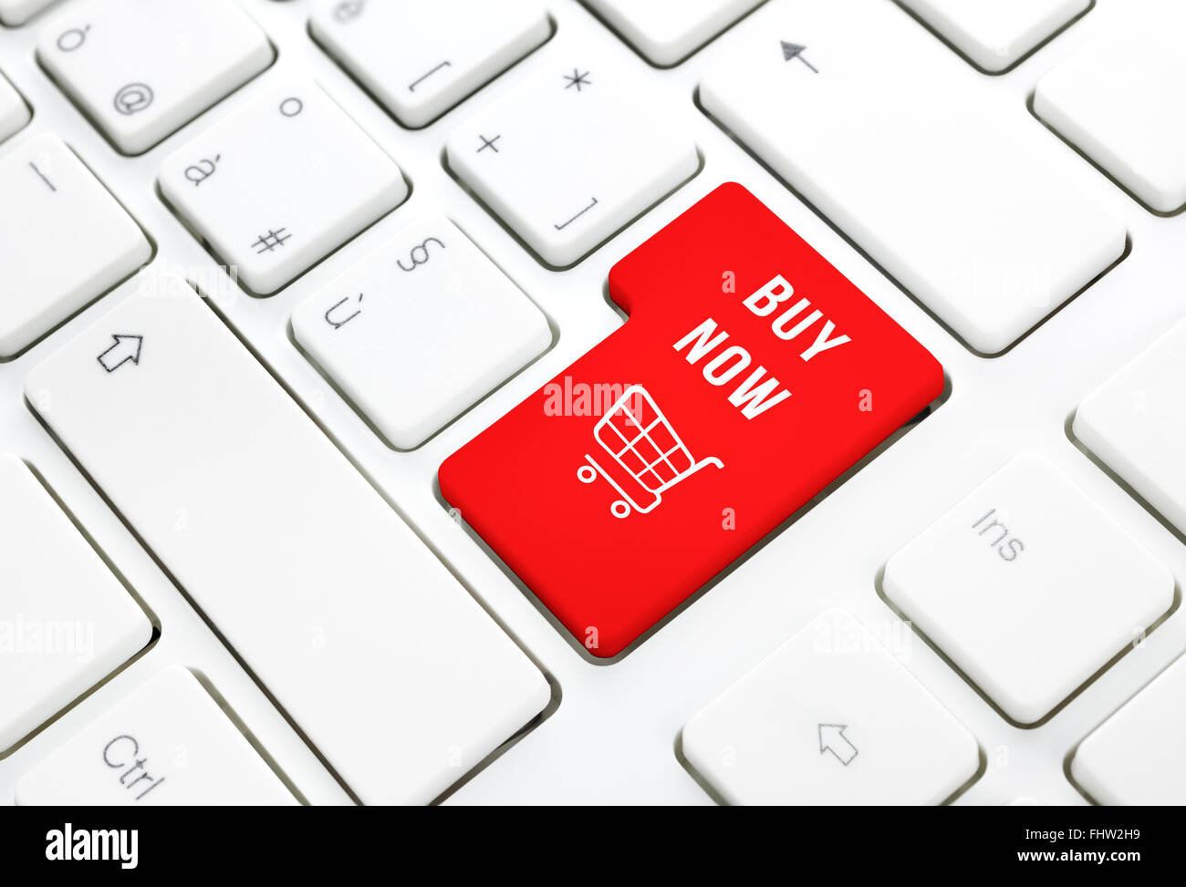 Shop online buy now business concept, Red shopping cart button or key on white keyboard photography. - Stock Image