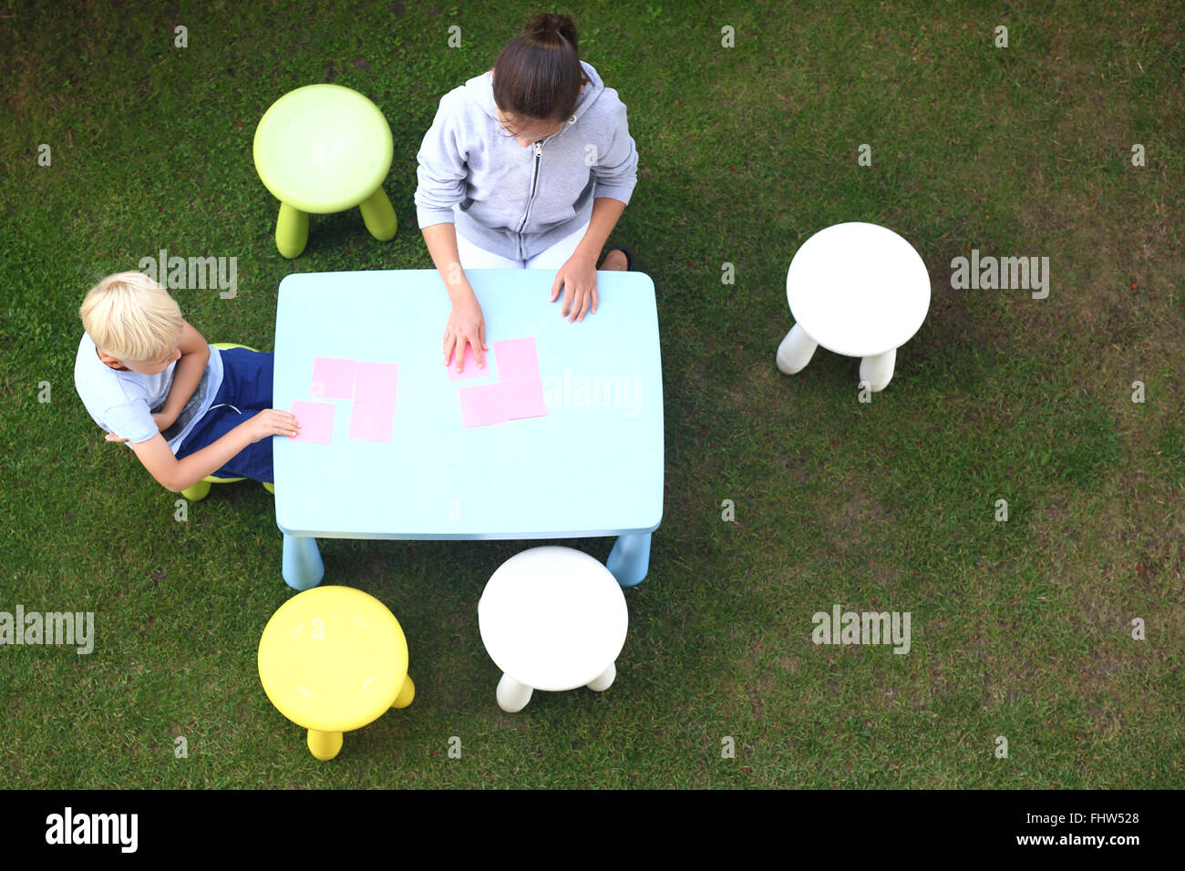 Fun outdoor activities. Creative fun way to boredom. Children play in the garden, they draw with crayons - Stock Image