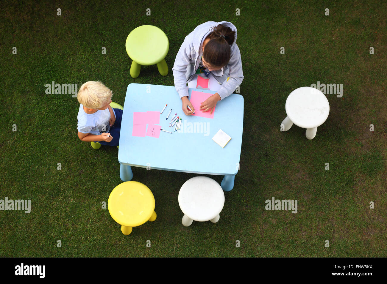 Fun outdoor activities. Creative fun way to boredom. Children play in the garden, they draw with crayons Stock Photo