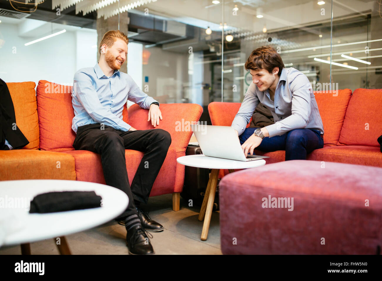 Business colleagues talking during break and working - Stock Image