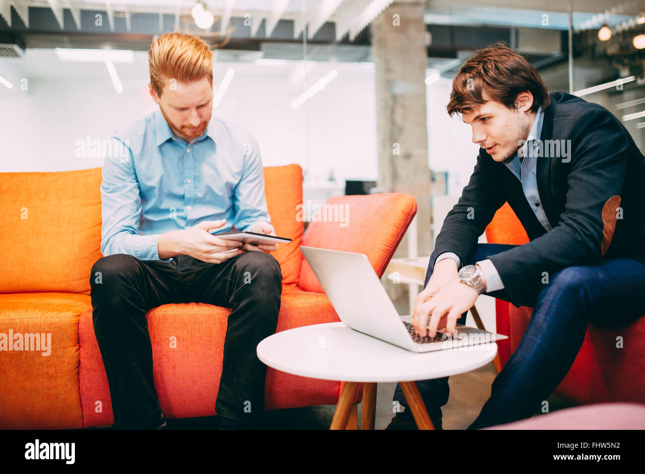 Business colleagues resting and talking during break - Stock Image
