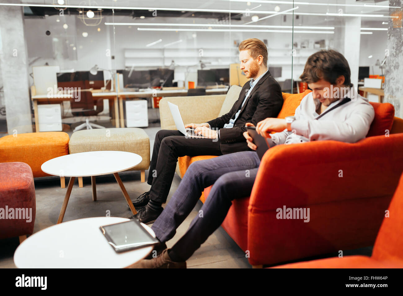 Businesspeople working while looking at devices and  laptops - Stock Image