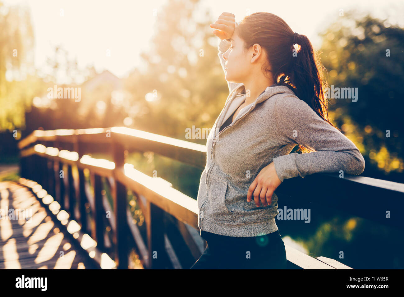 Beautiful female tired after jogging taking a break - Stock Image