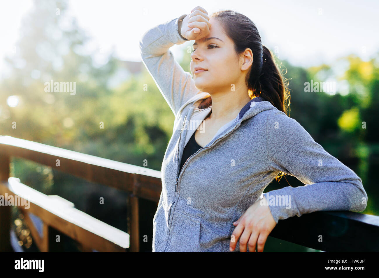 Beautiful woman resting after jogging outdoors and being exhausted - Stock Image