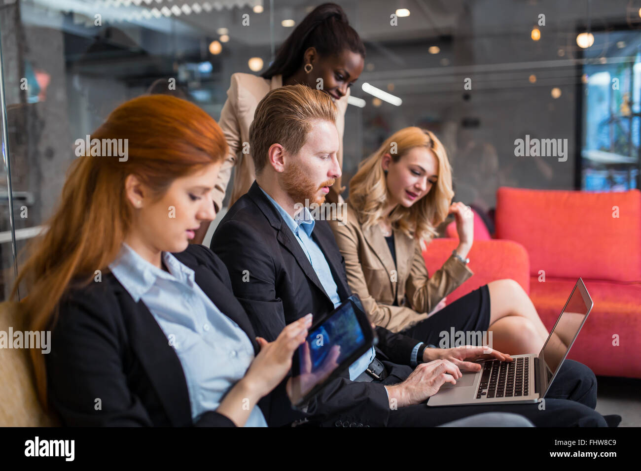 Business people conversation with technology at hand. Exchange of new ideas and brainstorming between colleagues - Stock Image
