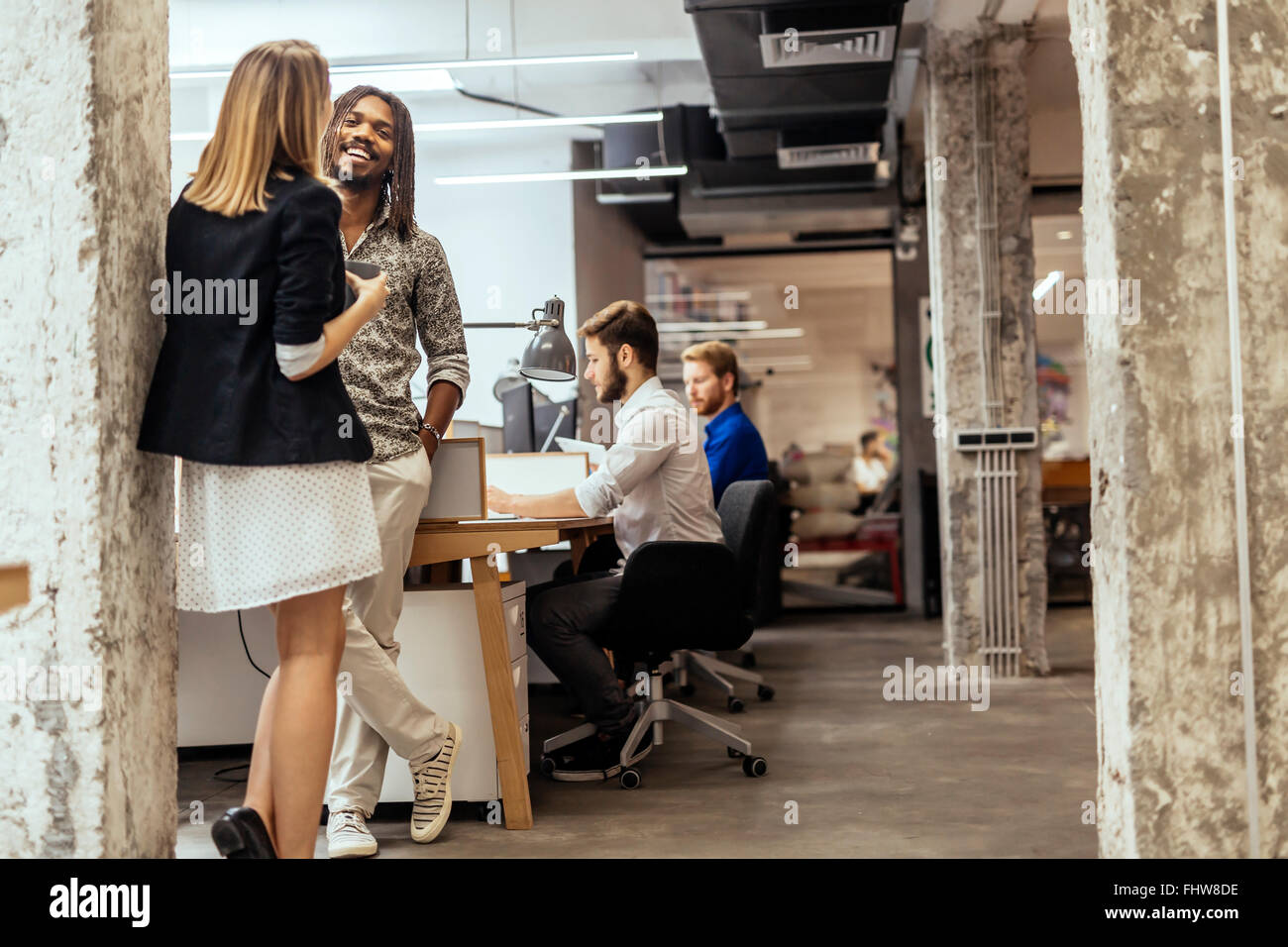 Business colleagues talking in the office  and smiling Stock Photo