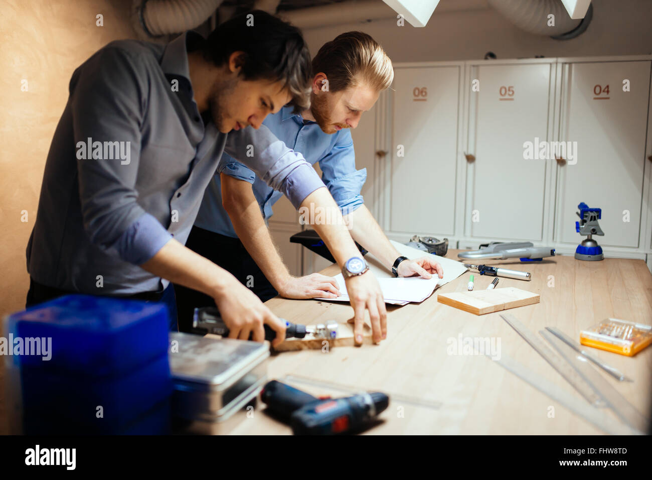 Two designers working together in workshop with precision tools - Stock Image