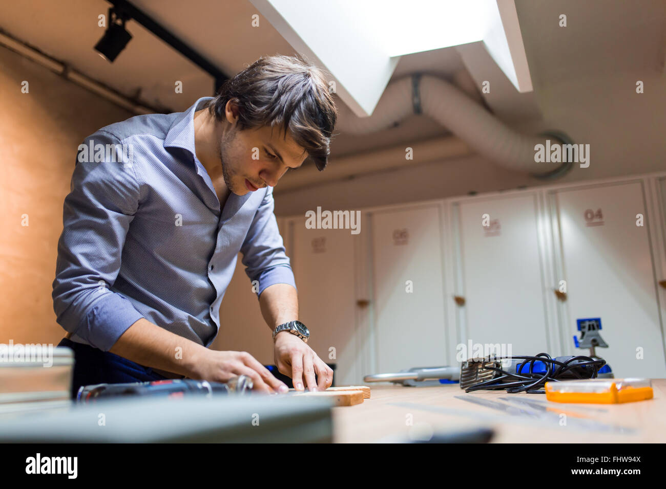 Joiner working and designing on workbench in workshop - Stock Image