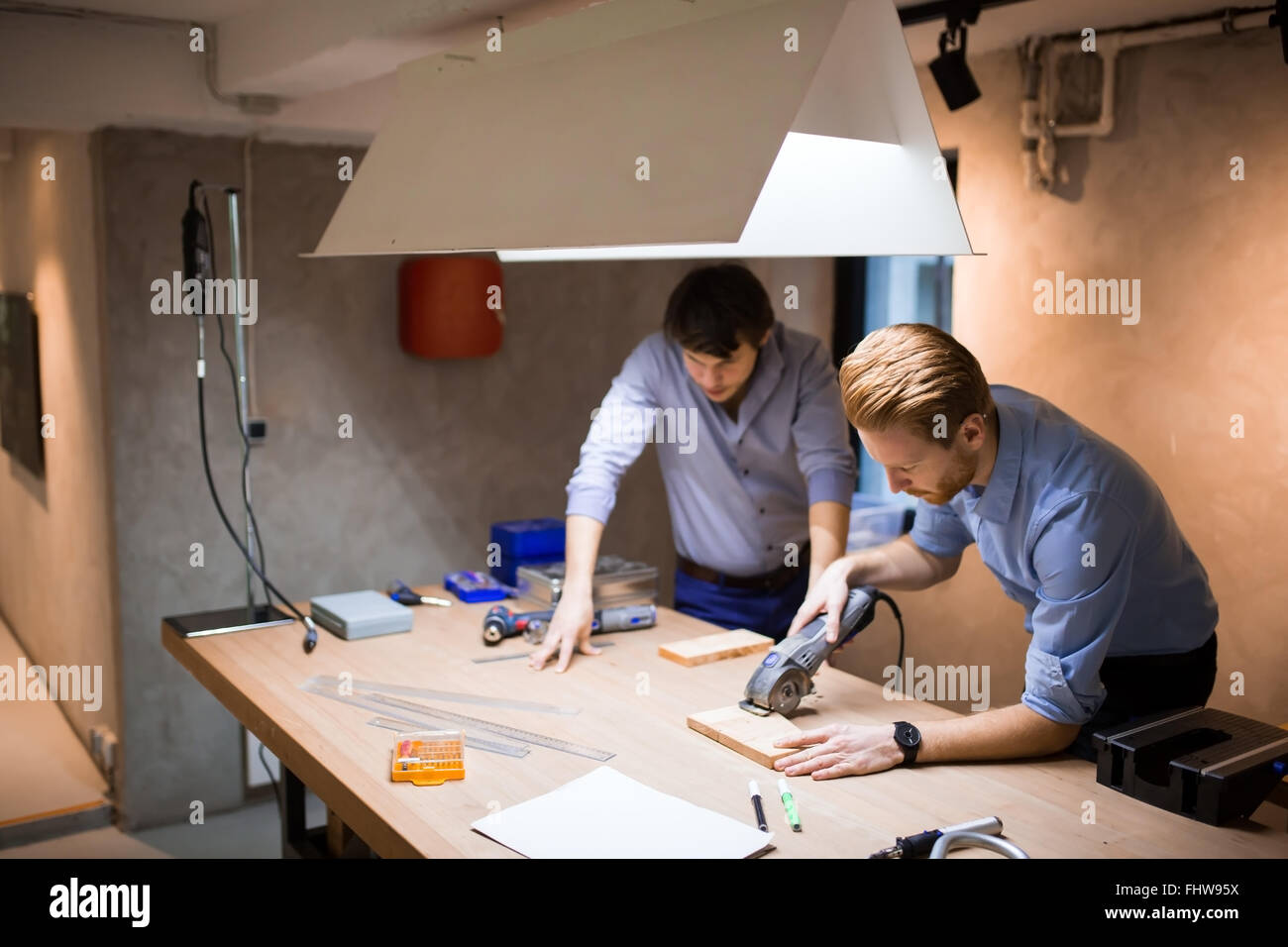 Two creative designers working in workshop with precision tools manufacturing a new product - Stock Image