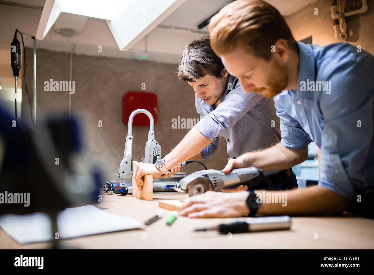 Two creative designers working in workshop and creating custom furniture - Stock Image