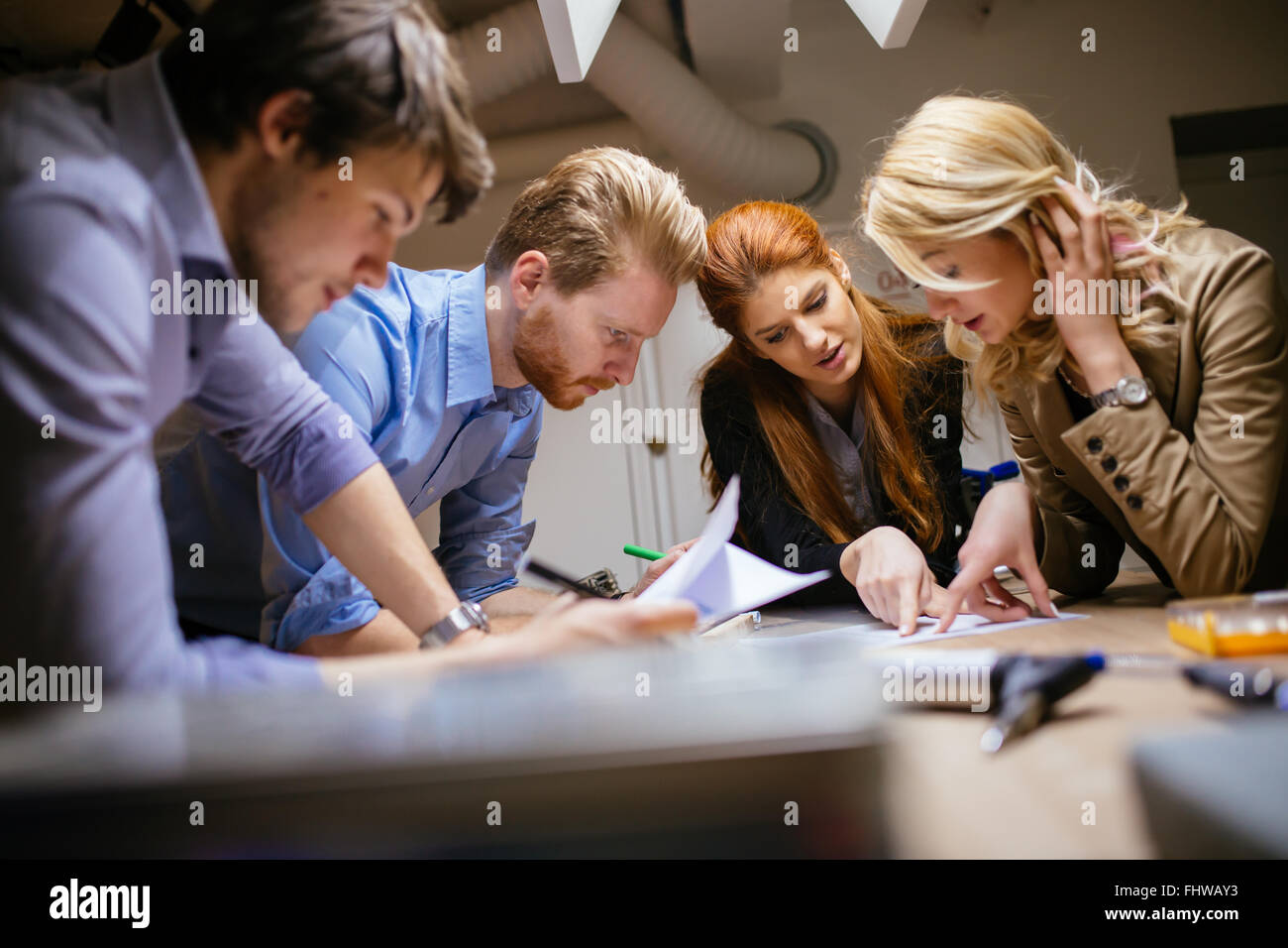 Creative workers designing and planing together in workshop - Stock Image
