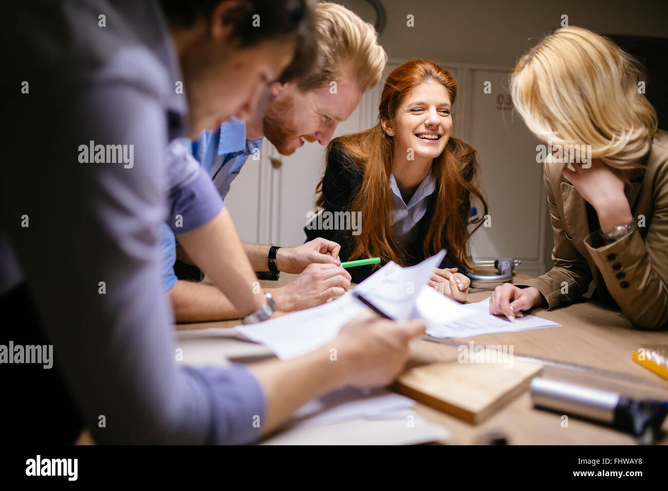 Classmates working on a project together and cooperating - Stock Image