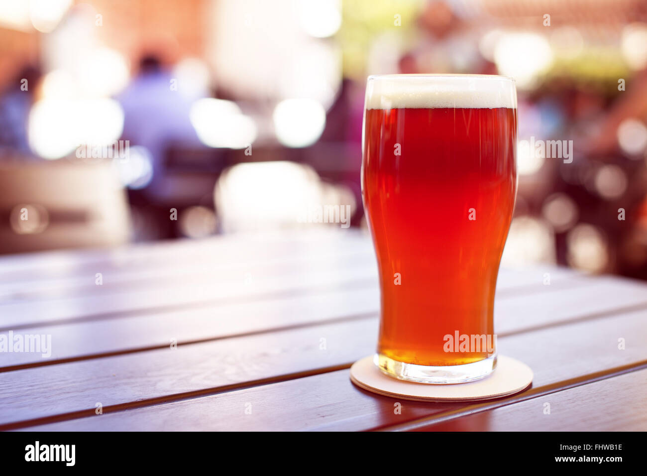 Pint of crafted ale on wooden table in beer garden - Stock Image