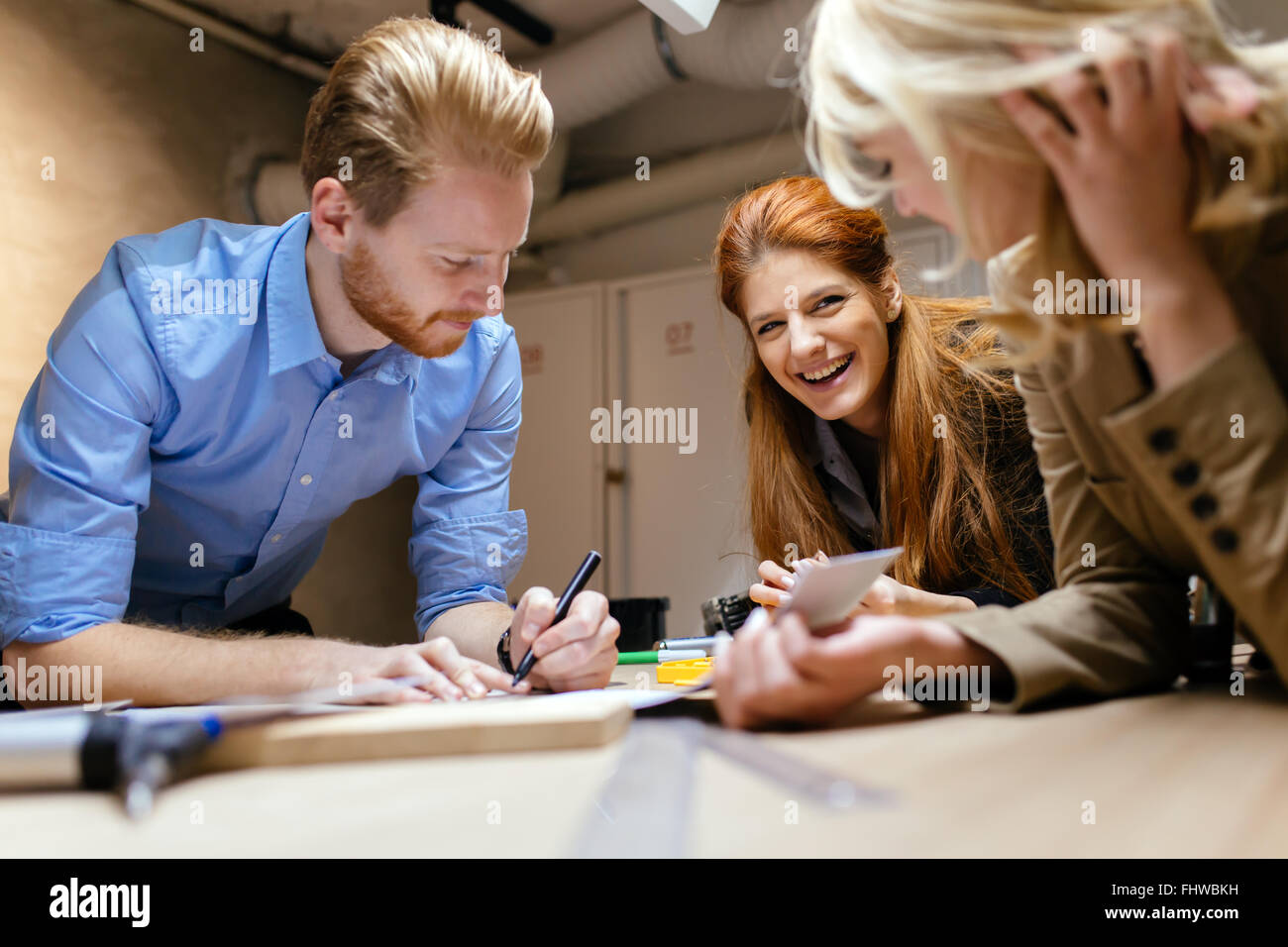 Team working on project together and sharing ideas in workshop - Stock Image