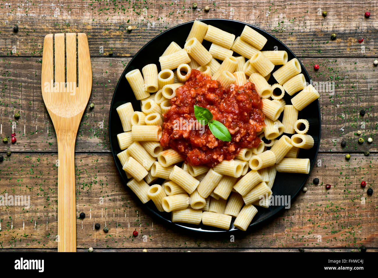 high angle shot of a wooden fork and a black plate with penne rigate with bolognese sauce on a rustic wooden table - Stock Image