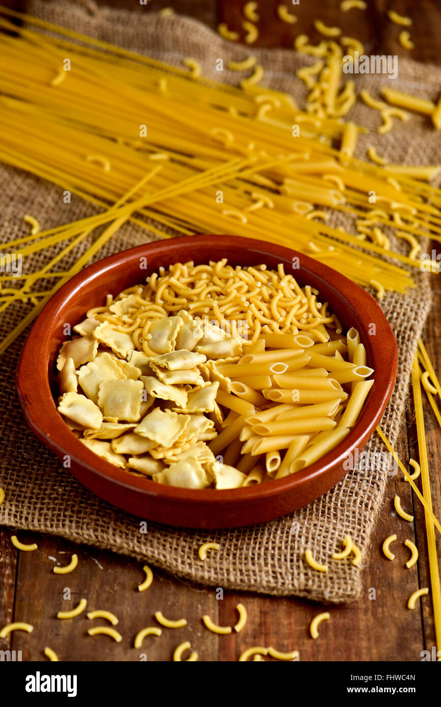 closeup of an earthenware bowl with different uncooked pasta such as ravioli, spaghetti or mostaccioli, on a rustic - Stock Image