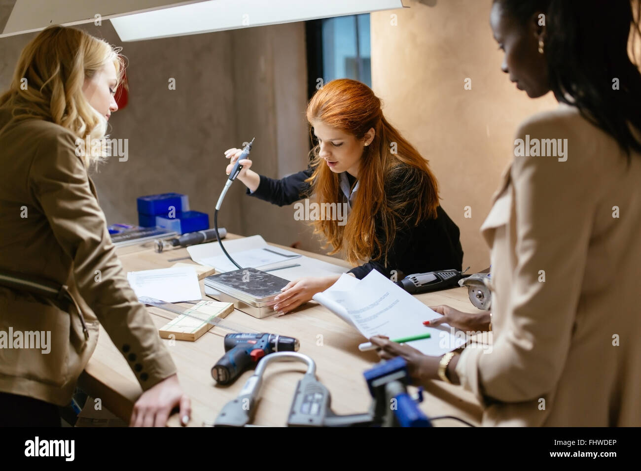 Creative women working on project and brainstorming in workshop - Stock Image