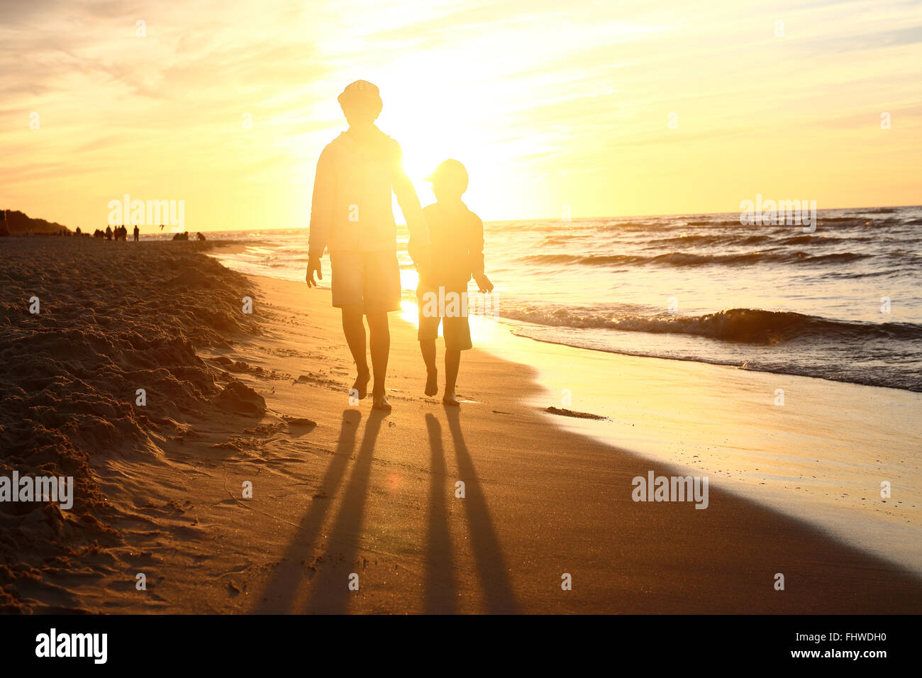 Walking on the beach, sunset. Children boy and girl playing on the sea shore on a sandy beach during sunset Stock Photo