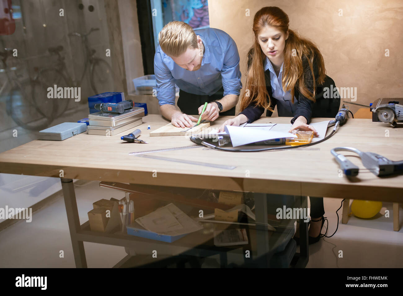 Designers working in modern office with handful of tools - Stock Image